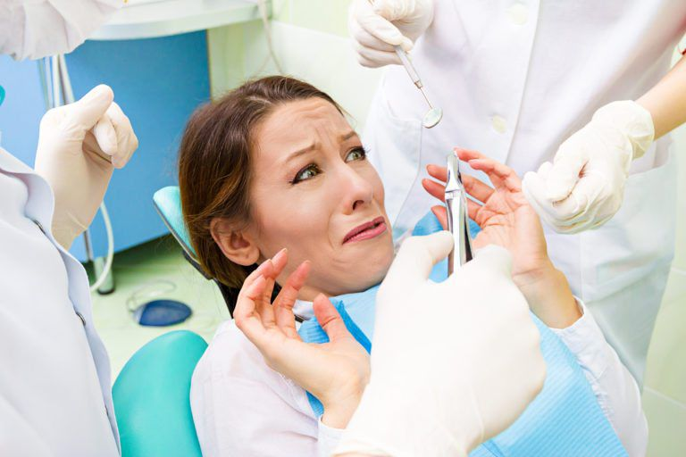woman sitting in dental chair nervously peering up at a hand holding a dental tool, looking very scared