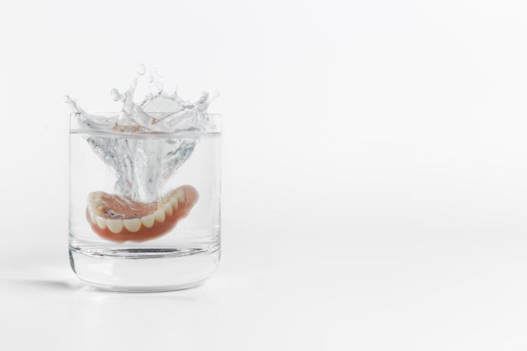 Dentures dropping into a cup of water
