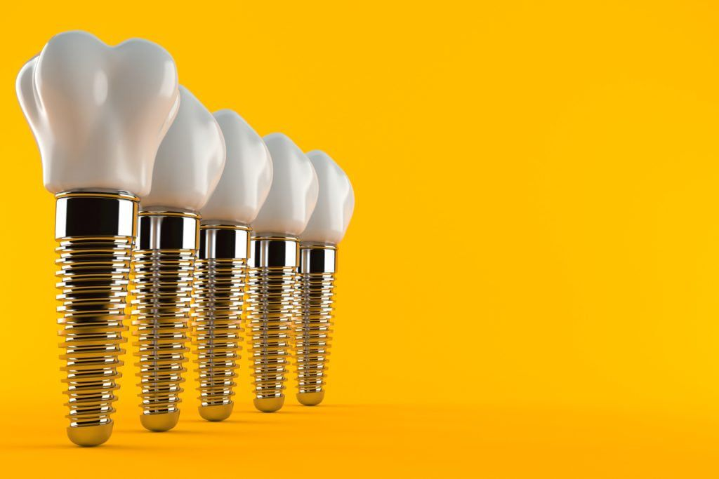 Dental implants on a golden yellow background